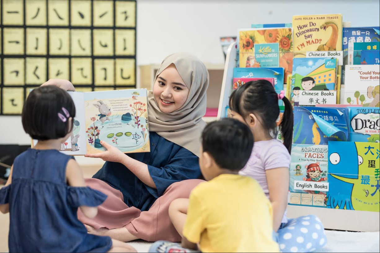 Lady reading story to 3 kids