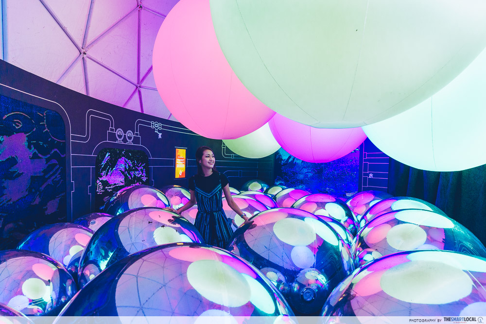 Girl surrounded by colourful giant baubles