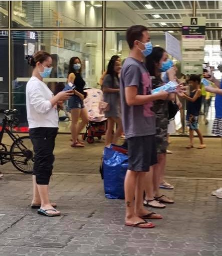 husband and wife giving out free masks
