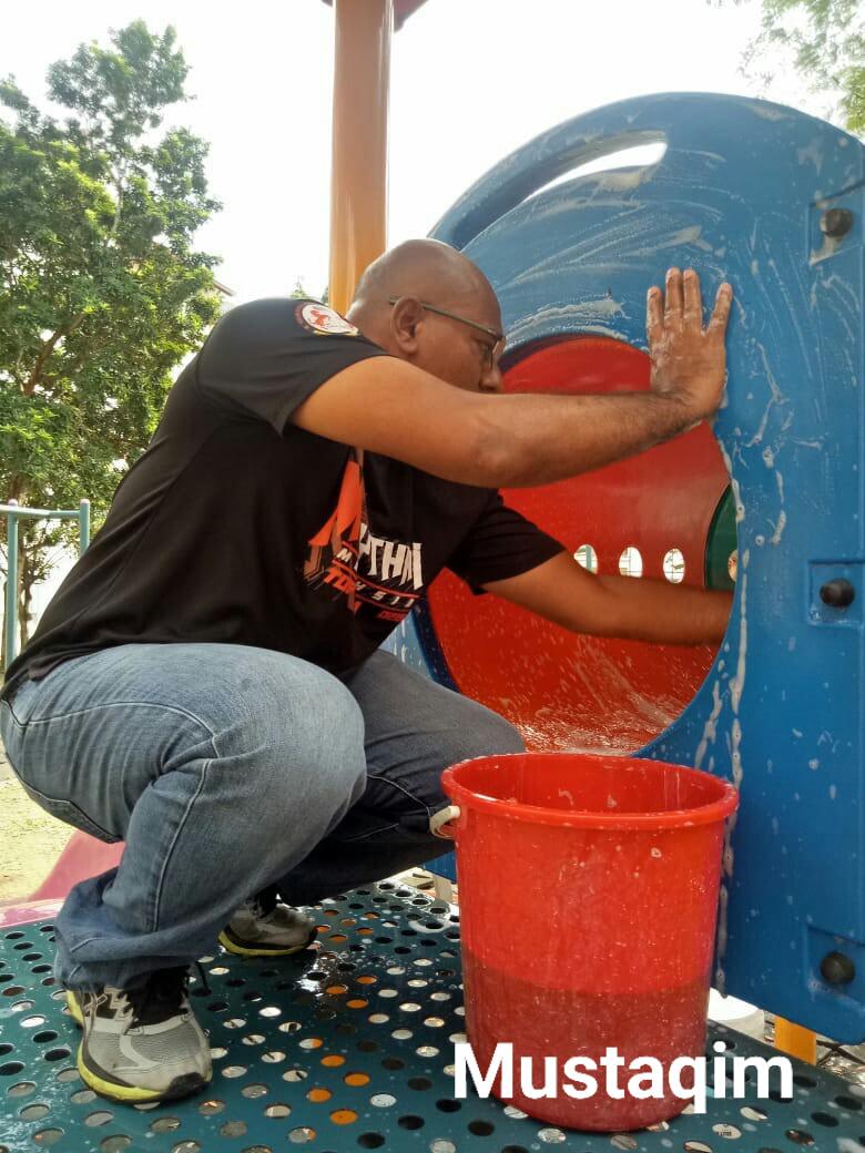 malaysian man washing playground