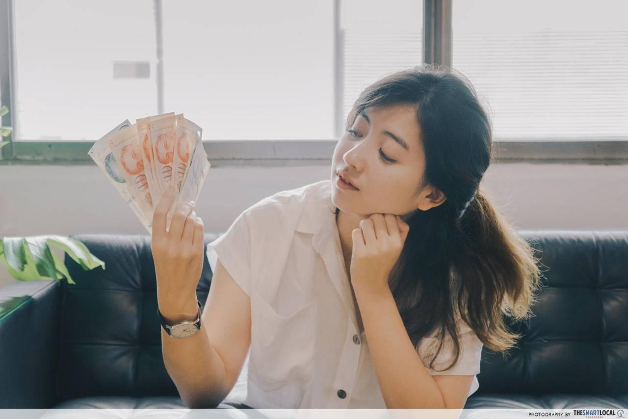 woman looking at singapore dollars