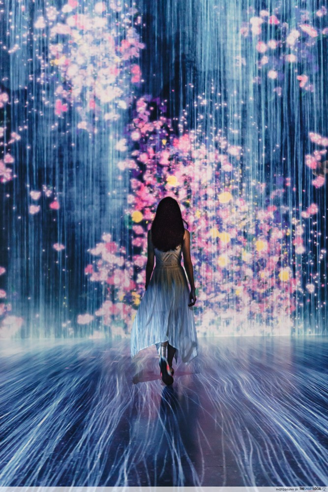 Image of woman standing in front of light projections at the Future World exhibit