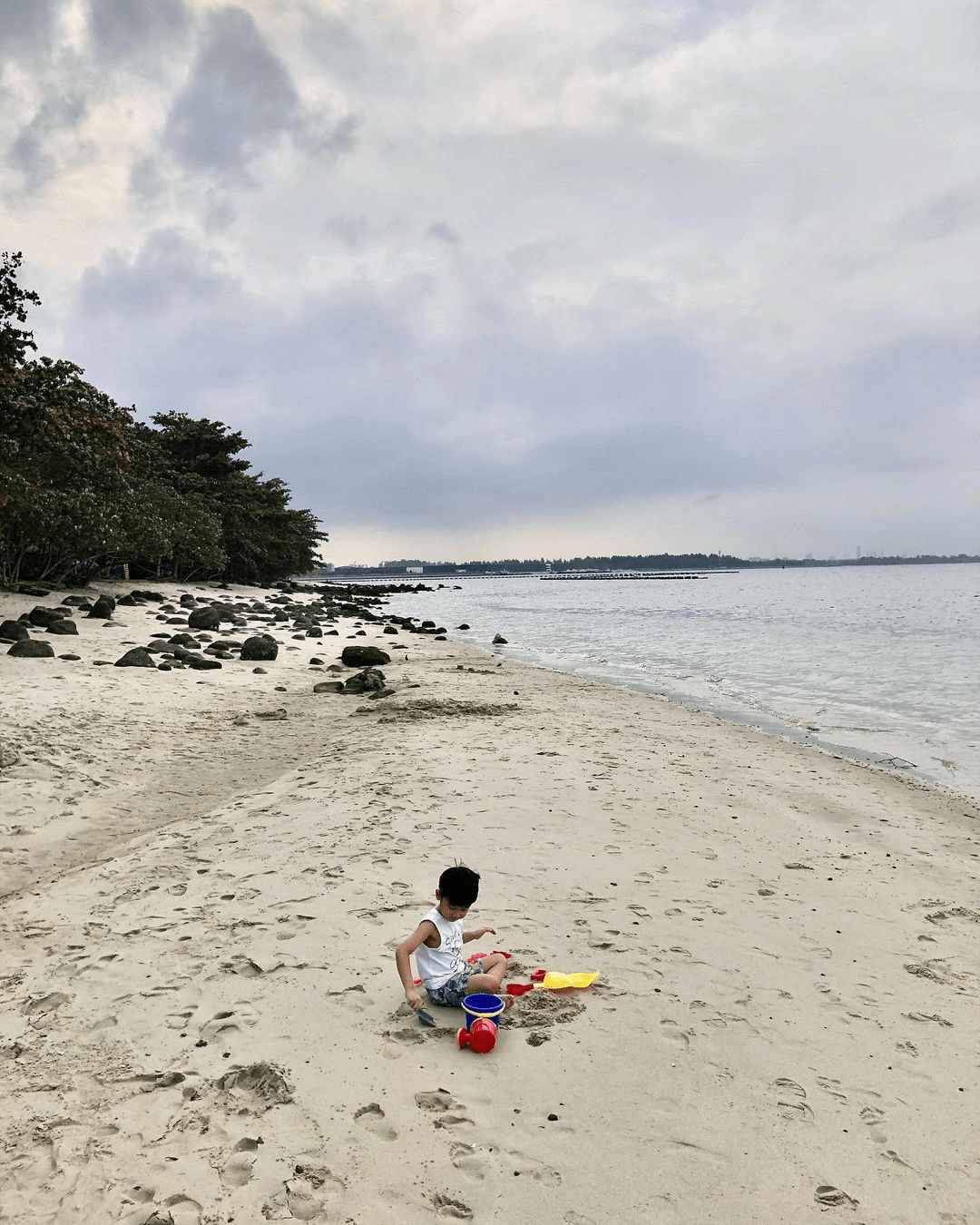 Child playing with the sand on Punggol Beach