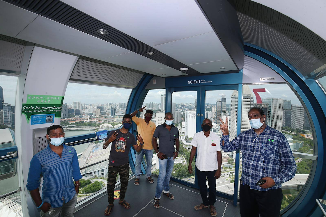 donate singaporediscovers vouchers - migrant workers on singapore flyer with itsrainingraincoats