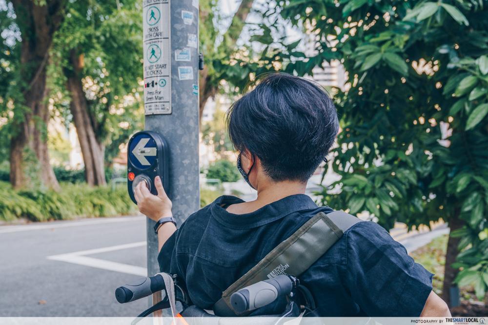wheelchair use pressing traffic button
