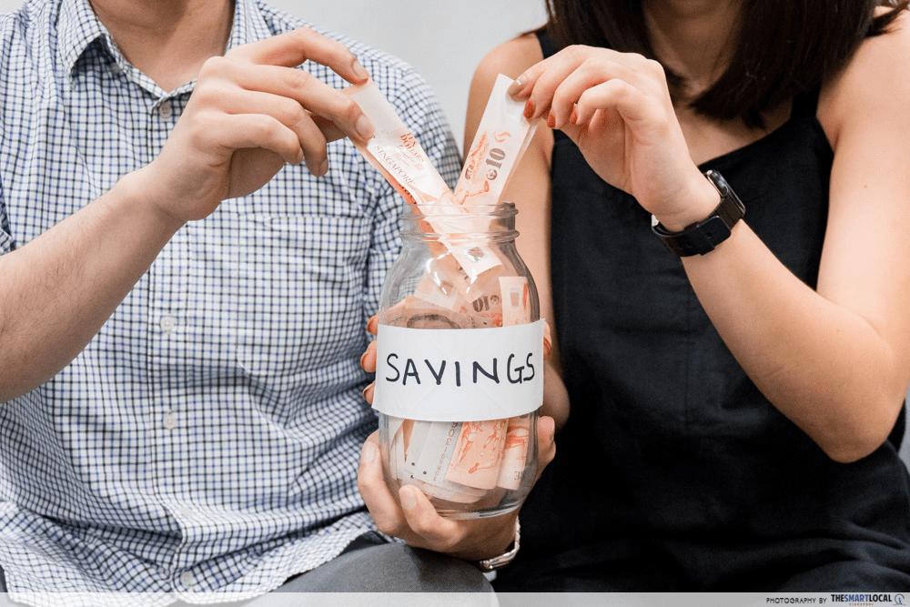 Couple putting money into savings jar