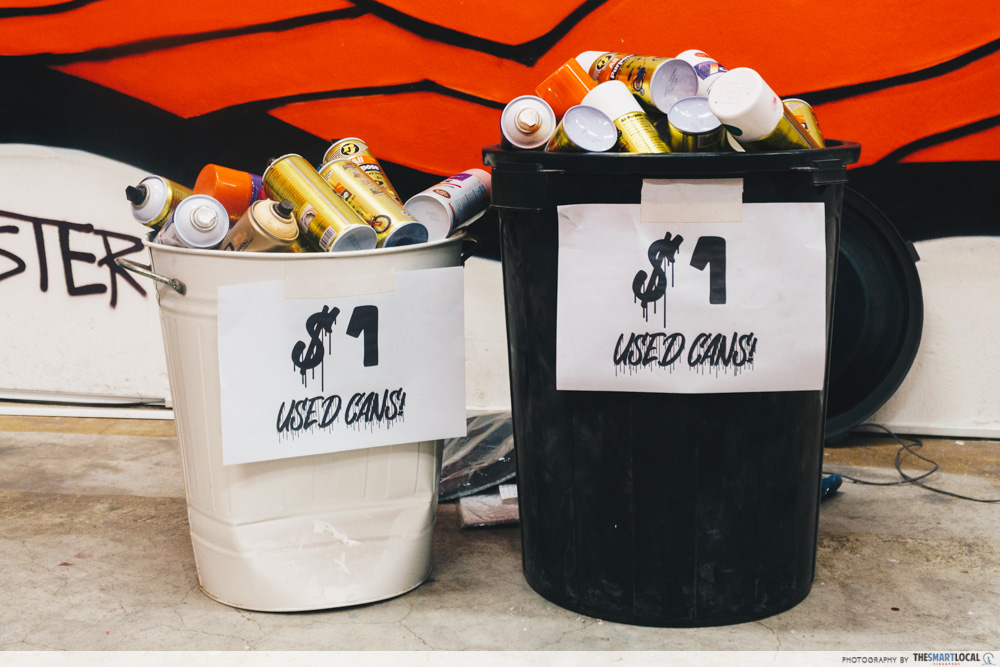 Bucket of used spray paint cans