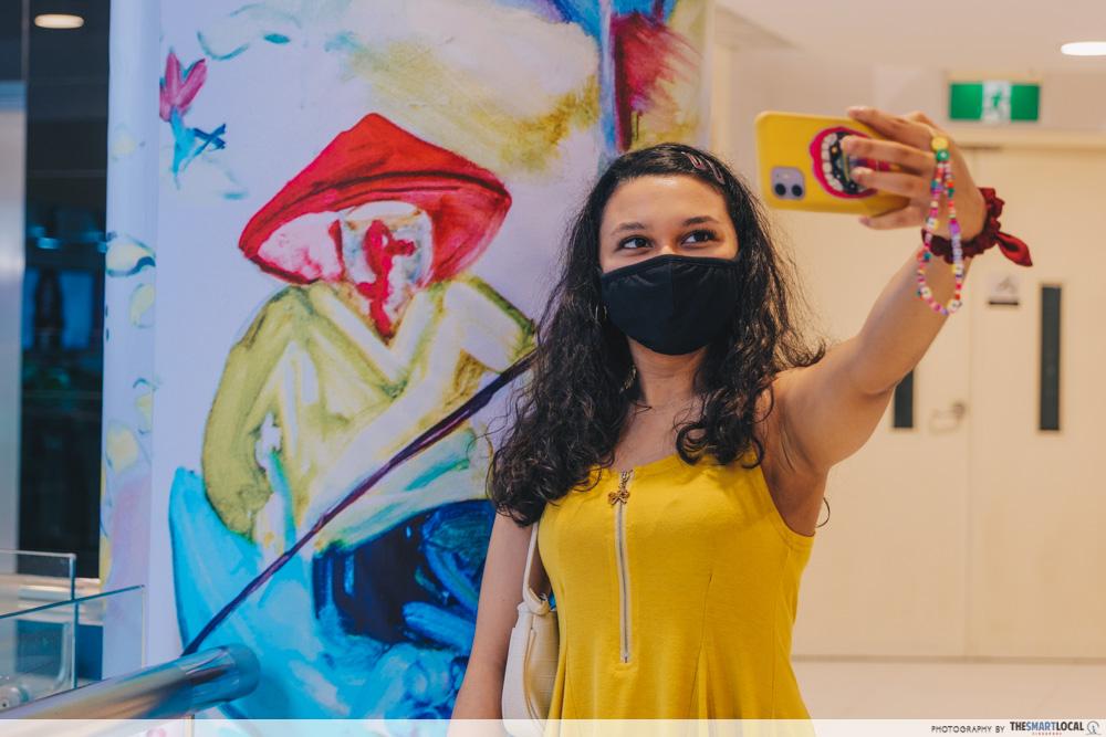 Girl taking selfie with hidden artwork