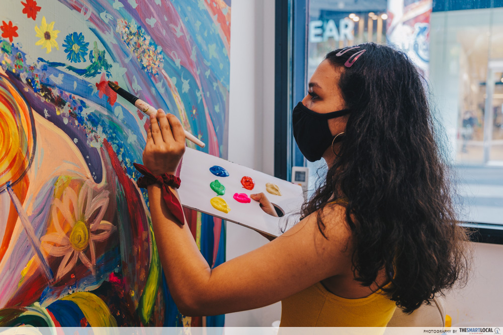 Girl painting on wall