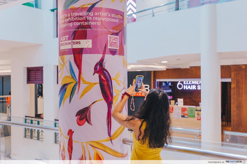 Girl taking photo of hidden artwork